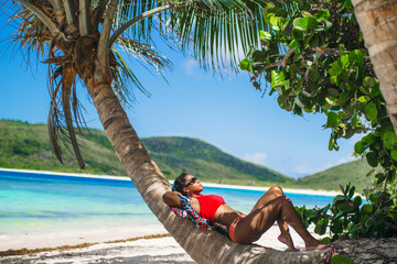 Woman relaxing on palm tree