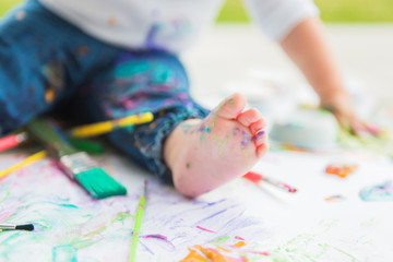 White toddler foot with splattered paint surrounded by paint brushes and paint covered paper.