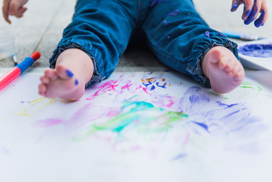 White toddler feet with splattered paint surrounded by paint brushes and paint covered paper.