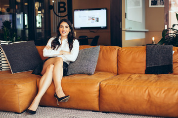 Portrait of smiling businesswoman sitting on sofa