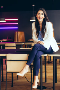 Portrait of smiling businesswoman sitting on the table in the office
