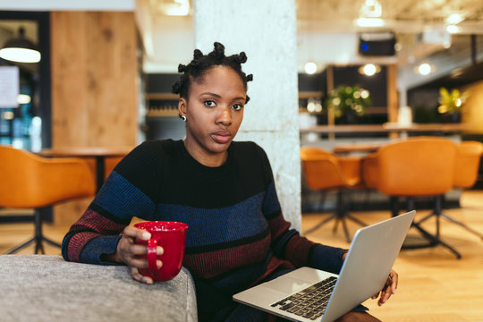 Portrait of young businesswoman working on laptop while having coffee