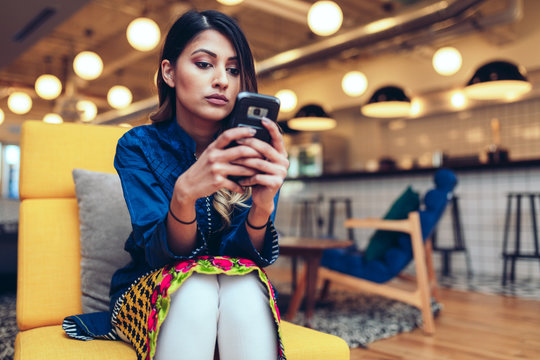 Young businesswoman using smartphone while sitting in office