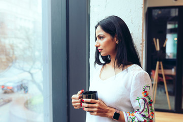 Young businesswoman looking out through window in office