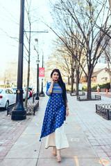 Portrait of young businesswoman walking on sidewalk