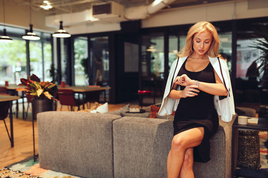 Businesswoman checking time  while sitting on office in office