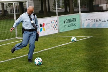 A United Nations security guard kicks a soccer ball on a pitch on the North Lawn before the start of a German-sponsored event at the United Nations headquarters promoting positive impact of the sport ahead of the World Cup, in Manhattan