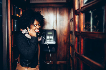 Young smiling woman in the telephone booth