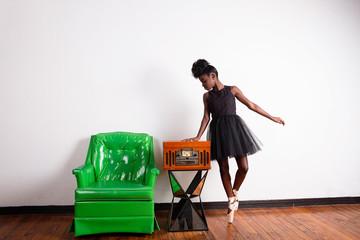 Ballerina posing near vintage console