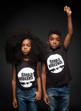 Portrait of children standing against black background