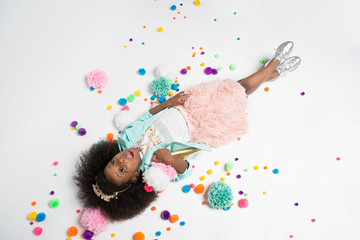 Overhead view of girl lying on white background