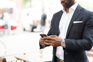 Mid section of businessman using smartphone while standing outdoors