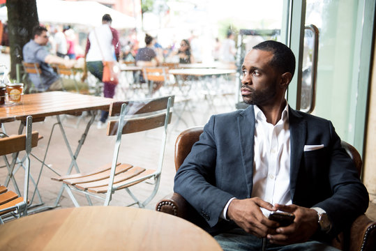 Businessman looking out through glass while sitting in cafe