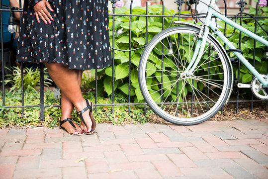 Low section of woman standing near bicycle