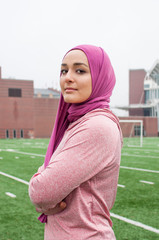 Portrait of young woman standing on soccer field