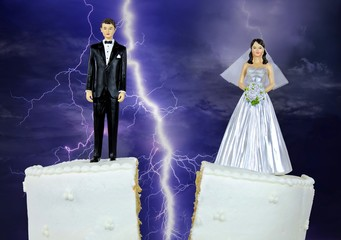 bride and groom figurine on split wedding cake with storm lightning background