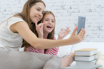 Mom and daughter giving kiss to the mobile phone screen while video calling with dad.