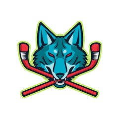 Sports mascot icon illustration of head of a coyote or gray wolf biting a crossed hockey stick viewed from front on isolated background in retro style.