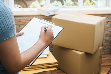 Happy woman checking stuff in cardboard box before sent to transportation company and movin