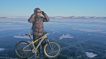 Man and his bicycle on ice. He stand and looks at the beautiful sunset. The cyclist is dressed in a gray down jacket, backpack and helmet. Ice of the frozen Lake Baikal. The tires on the bicycle are