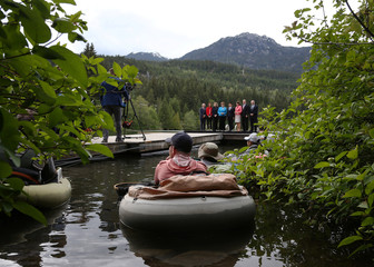 A fisherman watches as G7 delegates pose for a family photo at the G7 Finance Ministers summit in Whistler