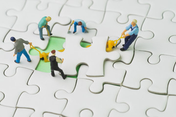 Teamwork, work as team for business success concept, miniature workers help using the forklift to complete the missing white jigsaw puzzle piece together on pastel green background