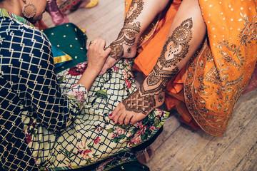 Process of applying traditional Mehndi henna on female leg. Close-up photo..