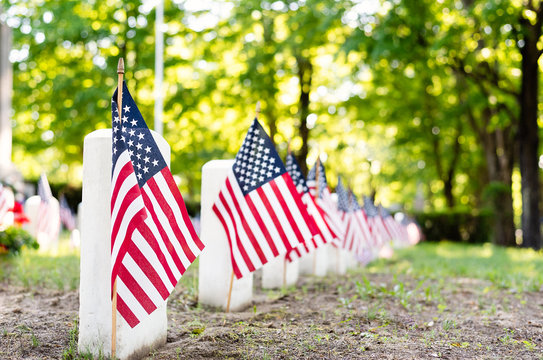 American flags marking the graves of war veterans in a cemetery