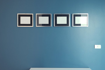 Four empty photo white frames hanging on the navy blue color wall