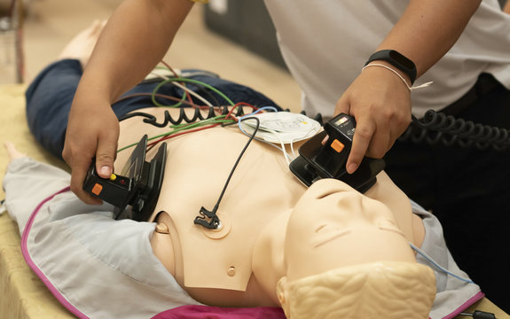 A male trainee performing defibrillation with a model on ACLS training course