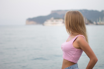 Portrait of unrecognizable young blonde woman looking at mountain by the sea