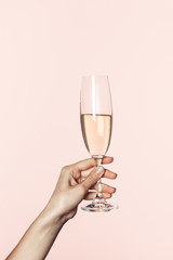 partial view of woman holding champagne glass isolated on pink background