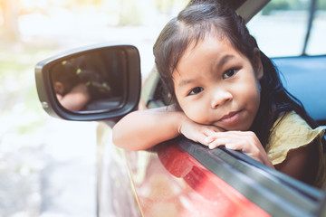 Cute asian little child girl smiling and having fun to  travel by car and looking out from car window in the countryside