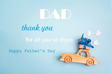 Father's Day greeting message with wooden toy car with a gift box on the roof on blue background