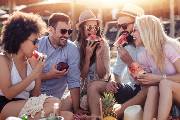 Group of friends eating watermelon on the beach
