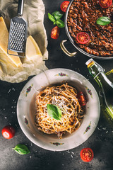 Spaghetti bolognese with ingredients basil tomatoesparmesan cheese and olive oil