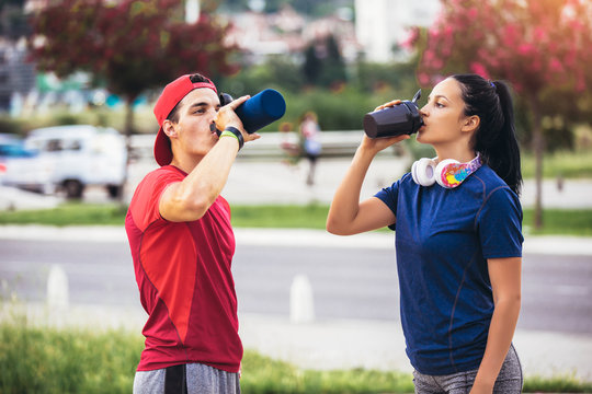 Couple drinking water after workout outdoor