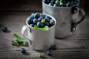 Sweet blueberry in the old metal mug on wooden table