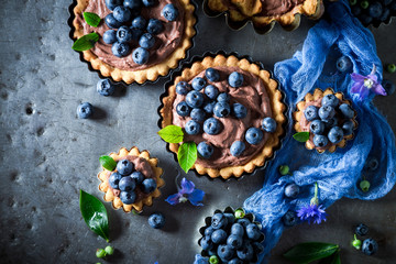 Sweet and tasty tarts with brown cream and fresh berries