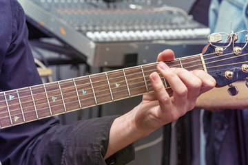 The hand of the guitarist on fingerboard