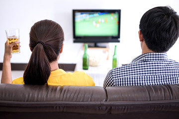 Young Asian couple love watching soccer match on tv and cheering football team, celebrating with beer and popcorn at home, sports and entertainment concept