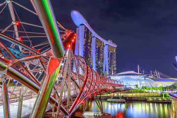 Singapore cityscape, Southeast Asia. Pedestrian bridge illuminated at night in the foreground in Marina Bay Area. Modern architecture in Sigapore city.