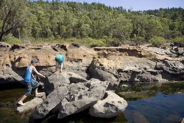 Two boys exploring a rocky rivers edge in Australia's great outdoors.
