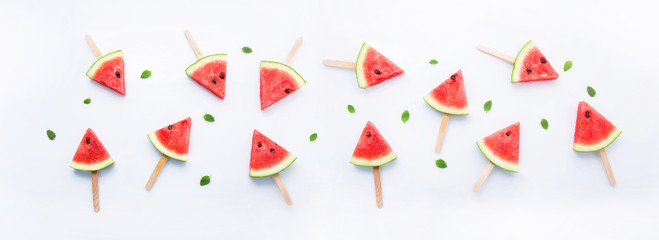 Watermelon slice popsicles on white background