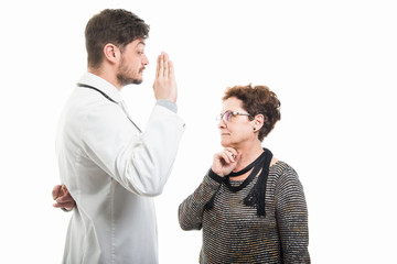 Male doctor and female senior patient showing fake oath gesture