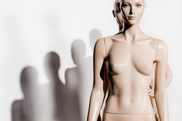 naked bald mannequins in a row and shadows on white