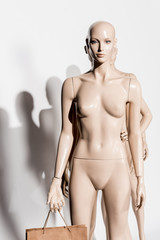 naked bald mannequin with shopping bag and shadow on white