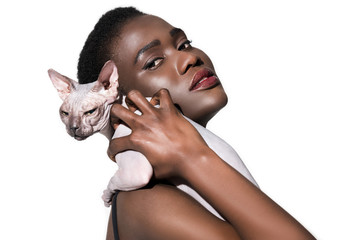 attractive young african american woman holding sphynx cat and looking at camera isolated on white
