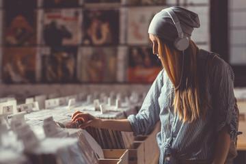 Spoed Foto op Canvas Muziekwinkel Young girl in a vinyl record store