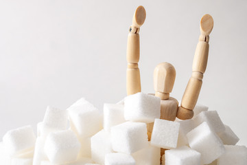 Sugar addiction, insulin resistance, unhealthy diet and November 14 is diabetes awareness day concept with a puppet drowning in sugar cubes isolated on white background and copy space for text Fototapete